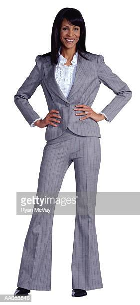businesswoman standing with hands on hips - gray pants stock pictures, royalty-free photos & images