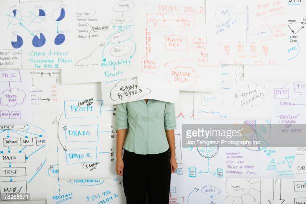 Businesswoman standing with head under flow chart