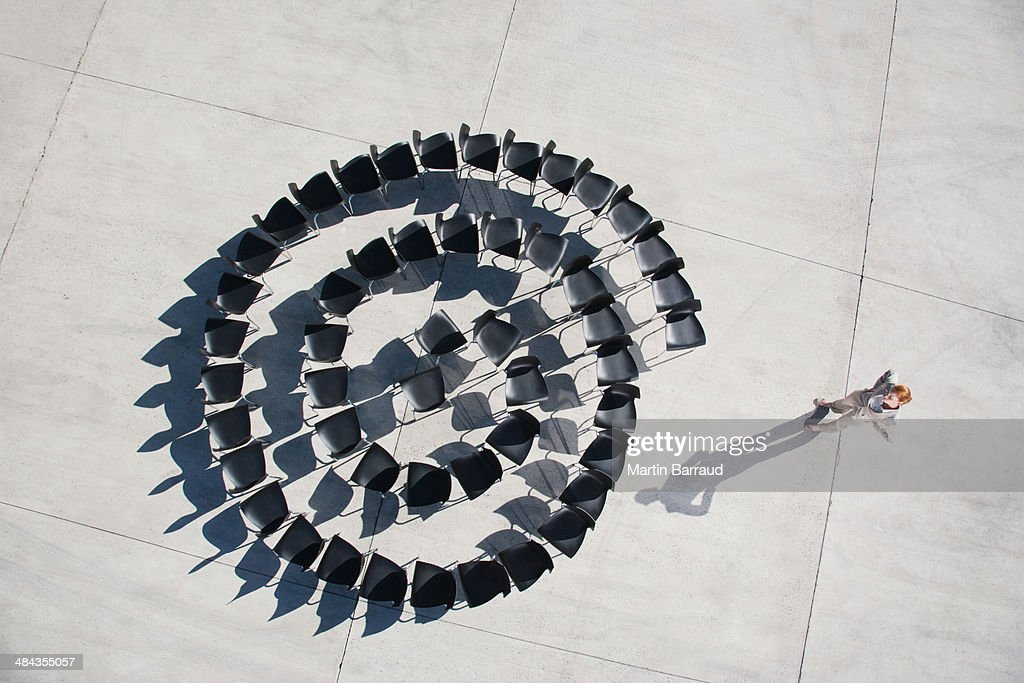 Businesswoman standing with spiral of office chairs : Stock Photo