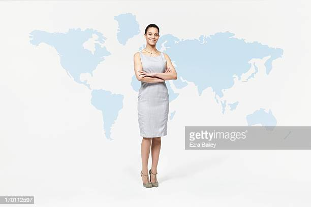 Businesswoman standing with world map.