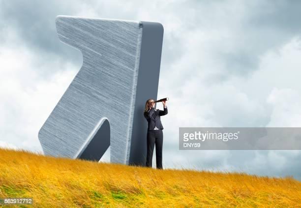 Geschäftsfrau steht vor großen Pfeil auf Wiese Blick durch Spyglass
