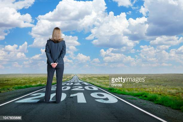 Businesswoman Stands On Long Road With Series Of Years Painted On It