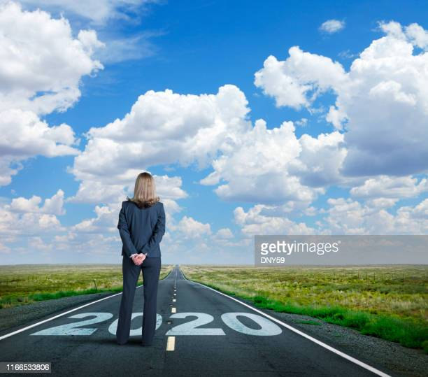 businesswoman stands on long road with the year 2020 painted on it - 2020 stock pictures, royalty-free photos & images