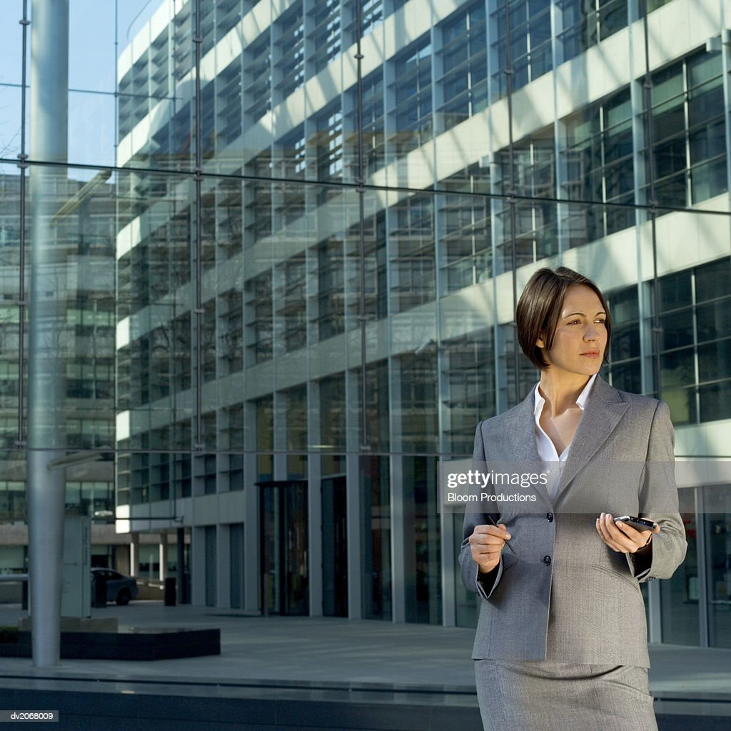 Businesswoman Stands Outside a Glass Building, Holding a Handheld PC : Stock Photo