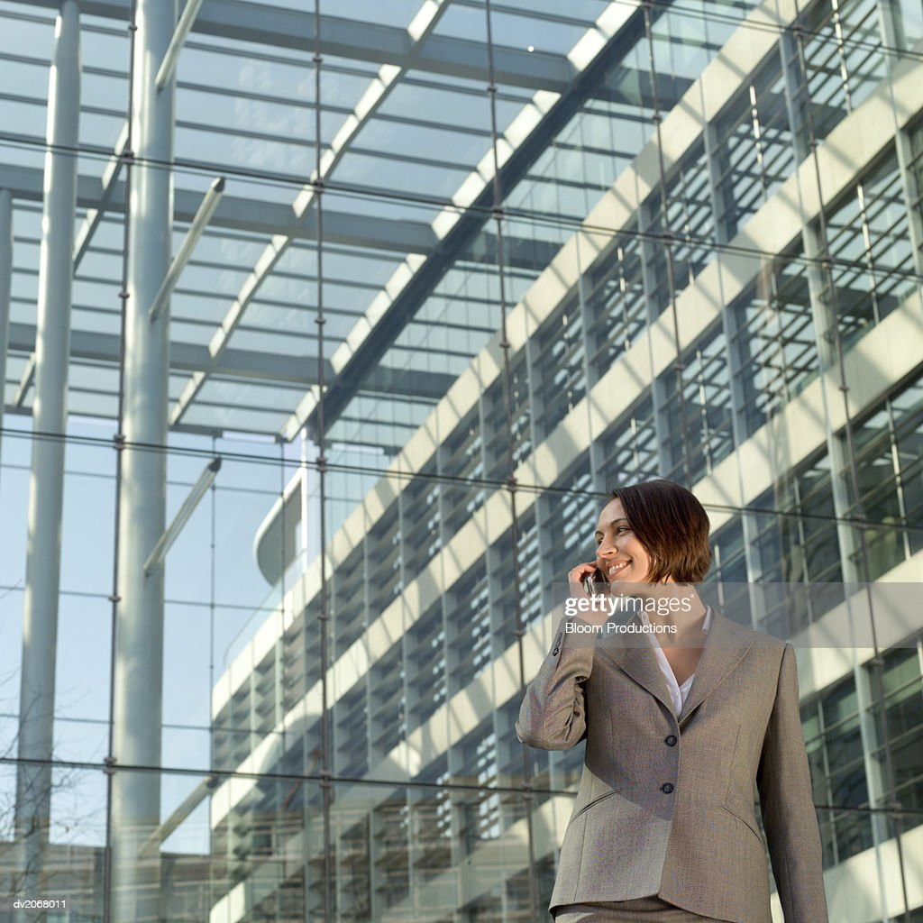 Businesswoman Stands Outside a Glass Building, Talking on Her Mobile Phone : Stock Photo