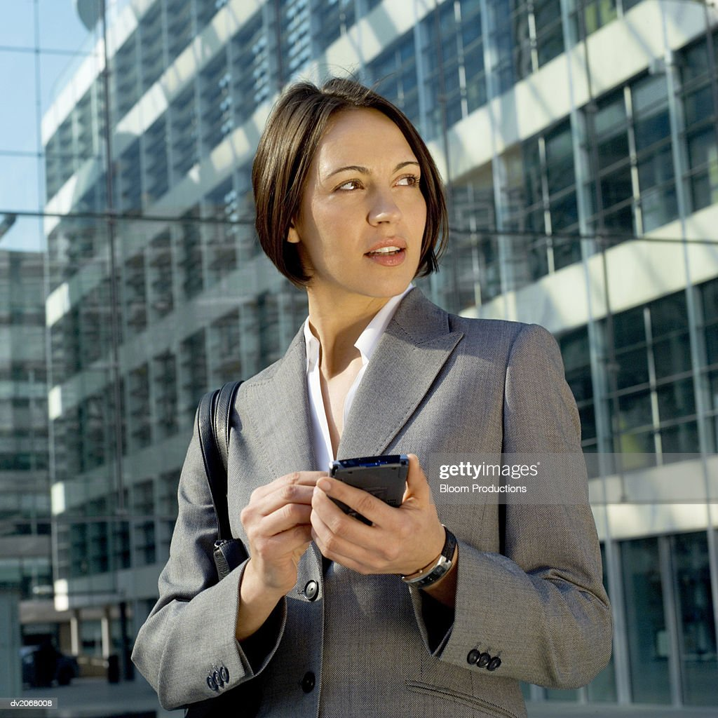 Businesswoman Stands Outside a Glass Building, Using a Handheld PC : Stock Photo