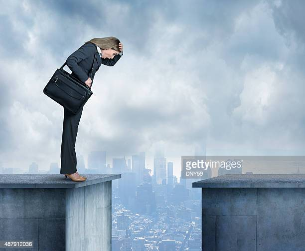 businesswoman stares at space between two buildings - bridging the gap stock photos and pictures