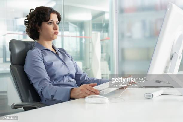 Businesswoman staring at computer monitor