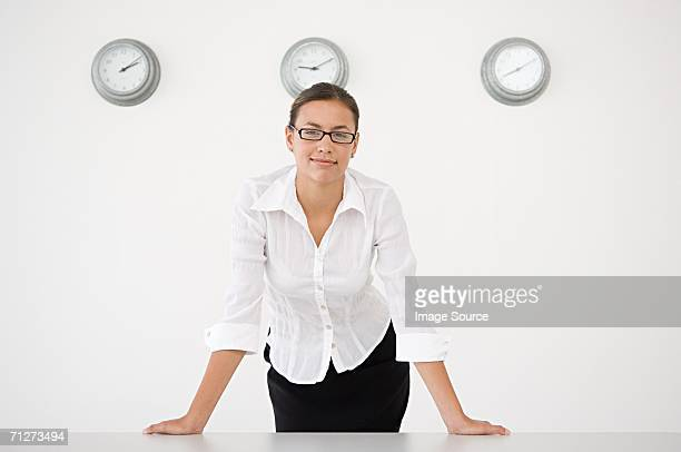 Businesswoman stood in front of three wall clocks