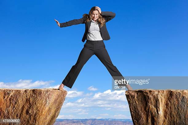 businesswoman straddling the divide created by two cliffs - legs apart stock photos and pictures