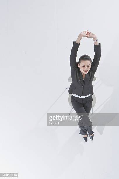 Businesswoman stretching arms on the chair