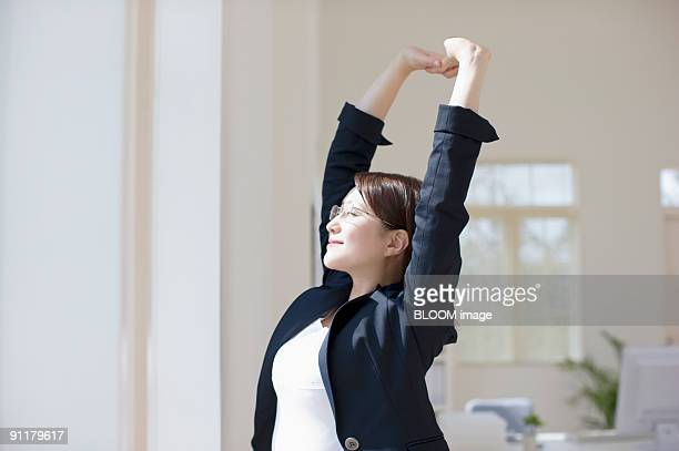 Businesswoman stretching arms