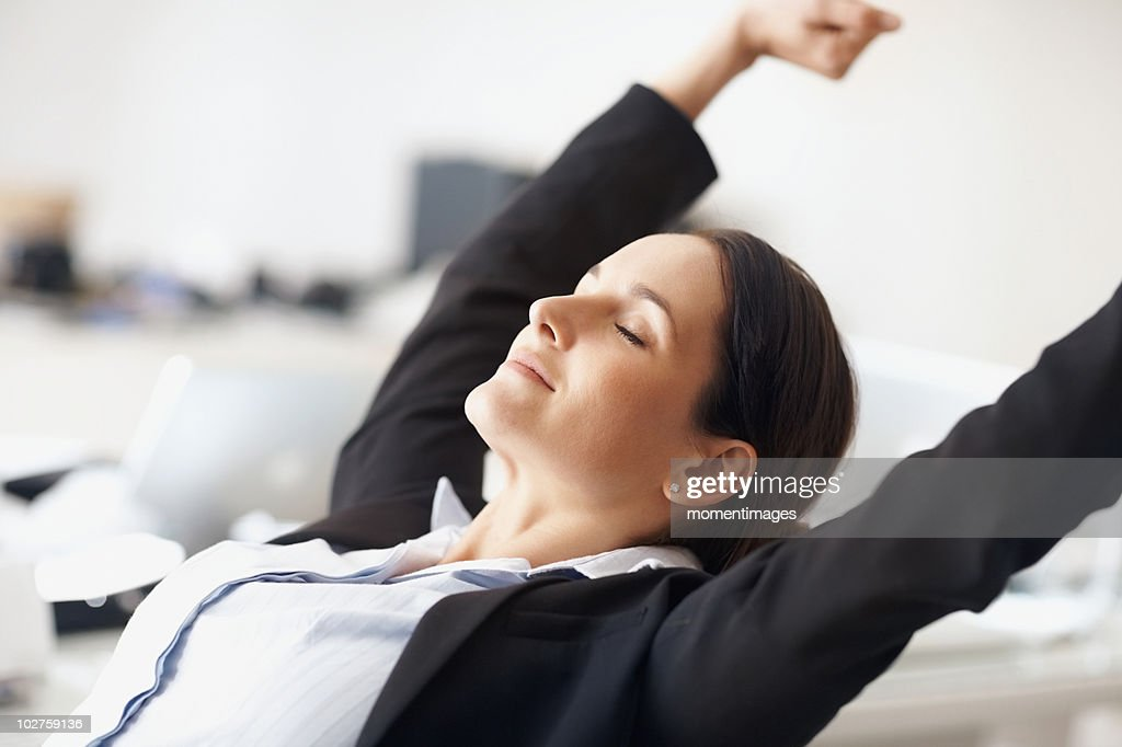 Businesswoman stretching at desk : Stock Photo