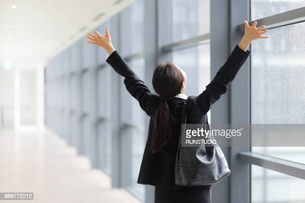 Businesswoman stretching at office window