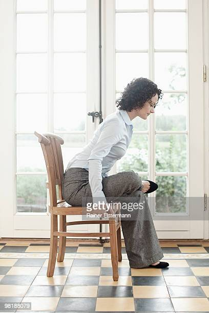 A businesswoman stretching on a chair