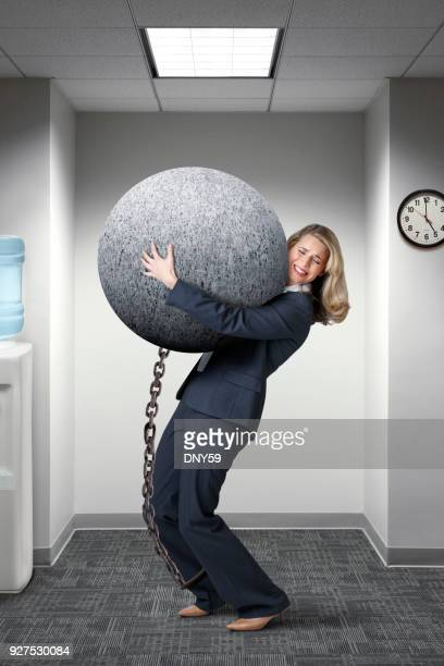 Businesswoman Struggles To Carry A Large Ball And Chain In Her Office