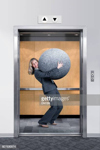Businesswoman Struggles To Carry Large Stone In An Elevator
