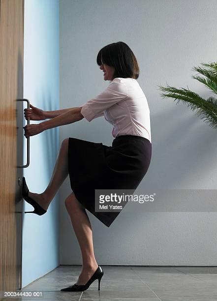 Businesswoman struggling to open door, foot against wall