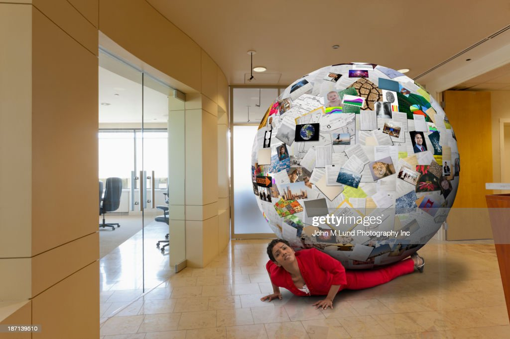 Businesswoman stuck underneath globe of images in office : Stock Photo