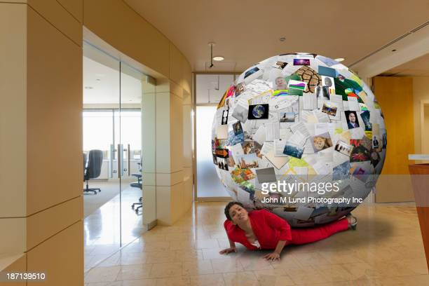 Businesswoman stuck underneath globe of images in office