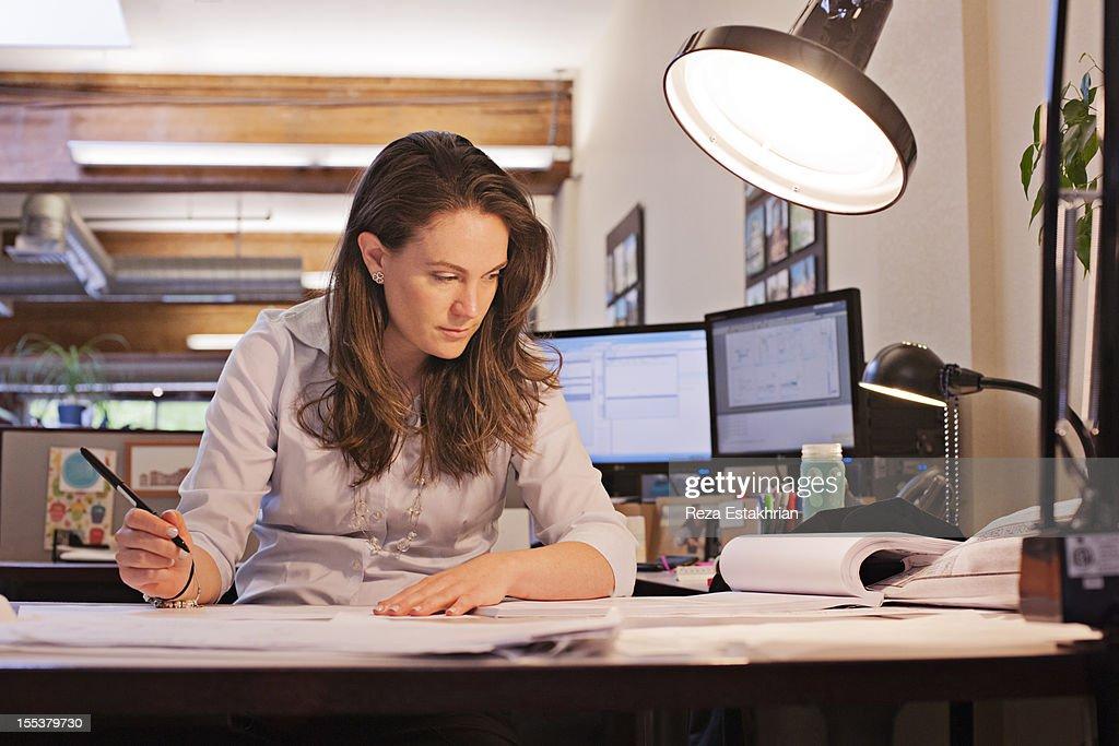 Businesswoman studies paperwork : Stock Photo
