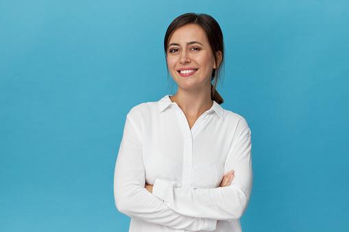 Businesswoman studio portrait. Confidence woman in elegant white shirt isolated on blue 1129386535