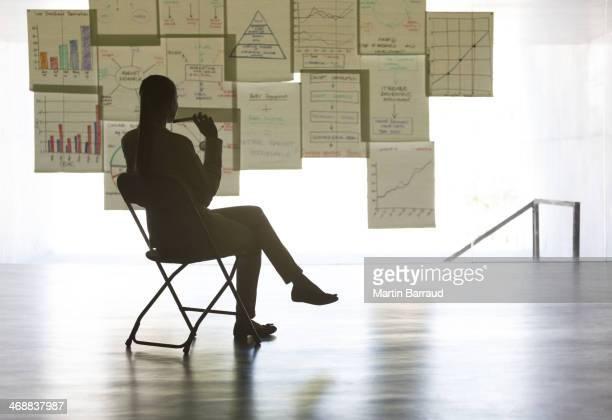 Mujer de negocios mirando tablas y gráficos en pared en oficina