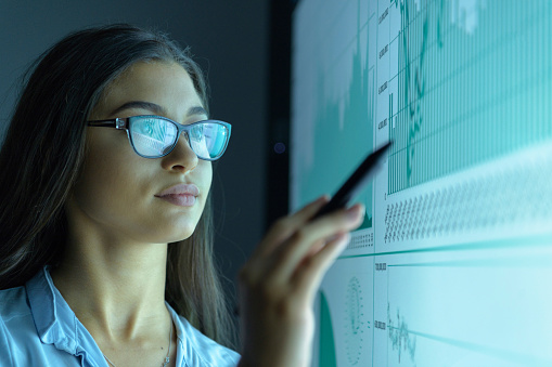 Businesswoman studying graphs on an interactive screen in business meeting - gettyimageskorea