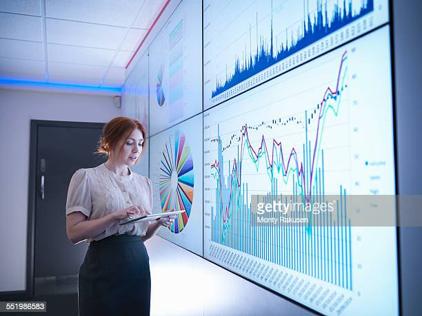businesswoman studying graphs on screen with digital tablet - projection screen stock photos and pictures