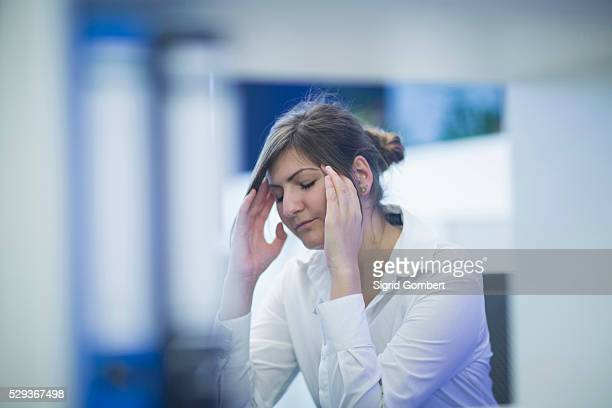 businesswoman suffering from a headache in an office, freiburg im breisgau, baden-w��rttemberg, germany - sigrid gombert stock pictures, royalty-free photos & images