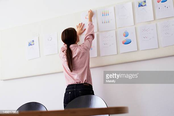 Businesswoman tacking up sign in office