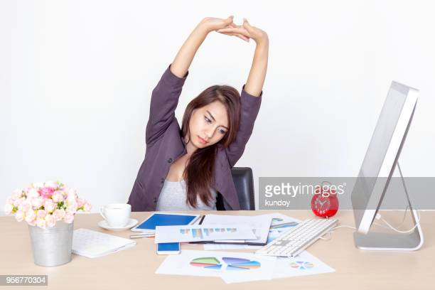 businesswoman take a break with muscle stretching while working in office. protect to office syndrome. - schlechte angewohnheit stock-fotos und bilder