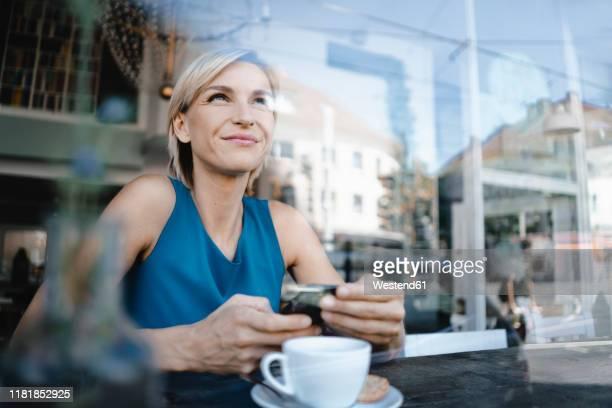 businesswoman taking a break in coffee shop, holding smartphone - red dress fotografías e imágenes de stock