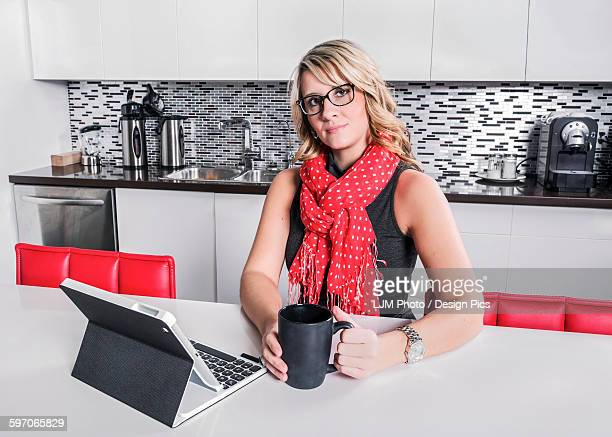 Businesswoman taking a coffee break and checking her tablet
