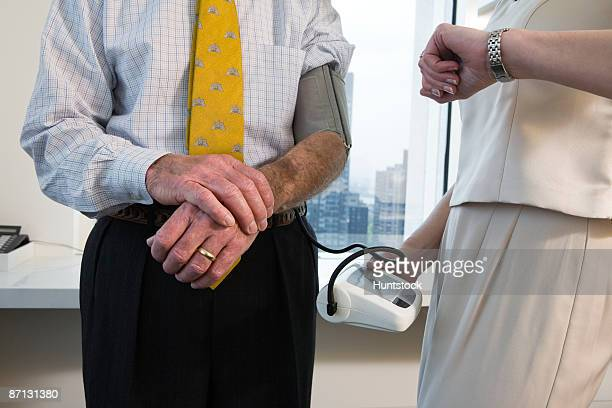Businesswoman taking businessman's blood pressure in an office