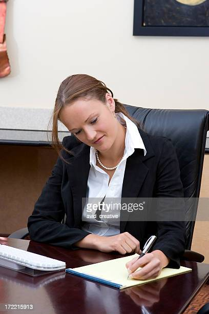 Businesswoman Taking Notes at Desk