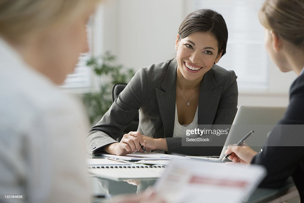 Businesswoman taking notes in a meeting : Stock Photo