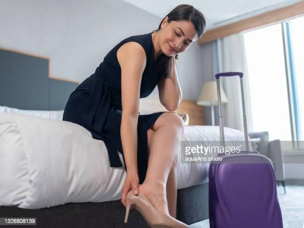 empresária tirando os sapatos depois de chegar ao quarto de hotel - salto alto - fotografias e filmes do acervo