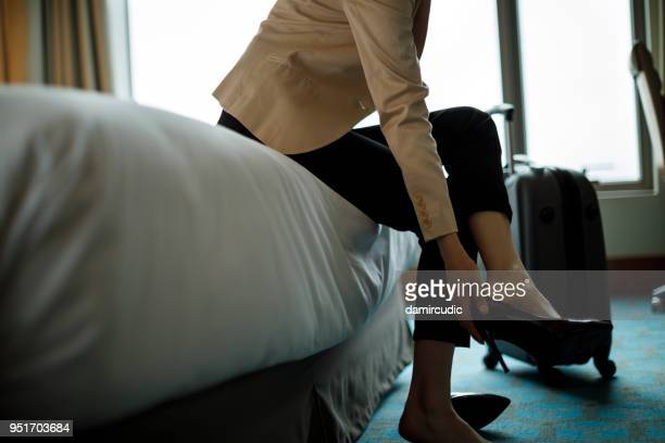 Businesswoman taking off shoes in a hotel room