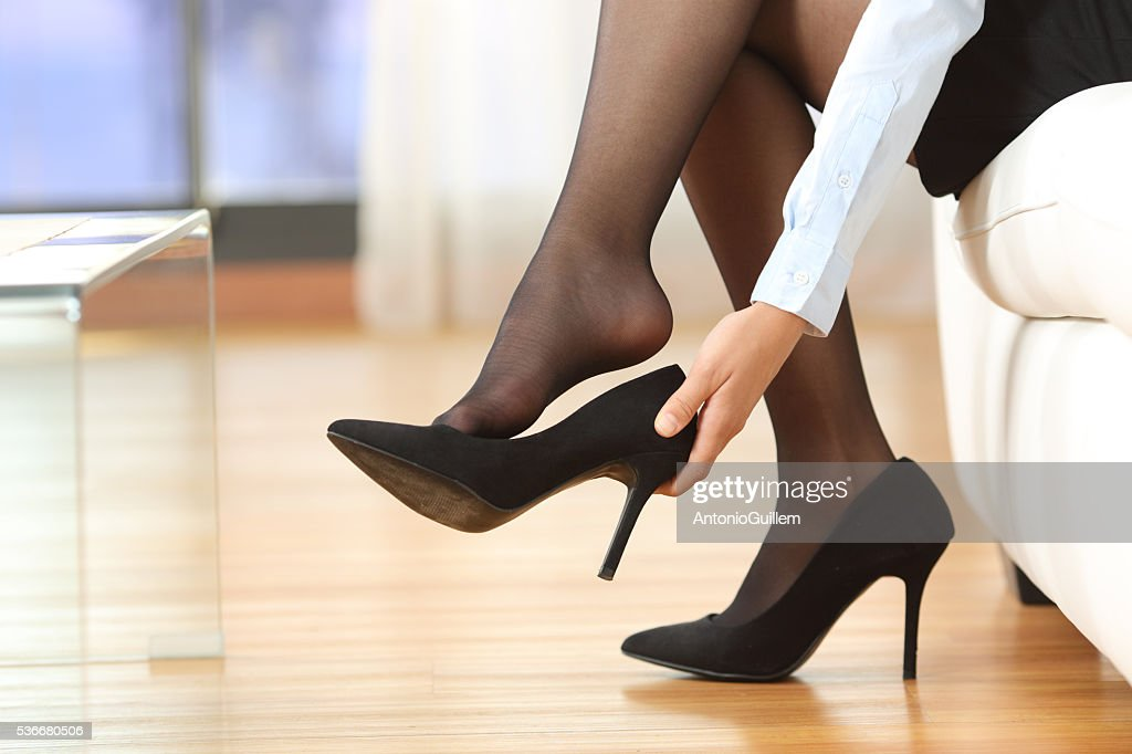 Businesswoman taking off shoes : Stock Photo