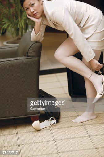 Businesswoman Taking Off Shoes While Standing Stock Photo