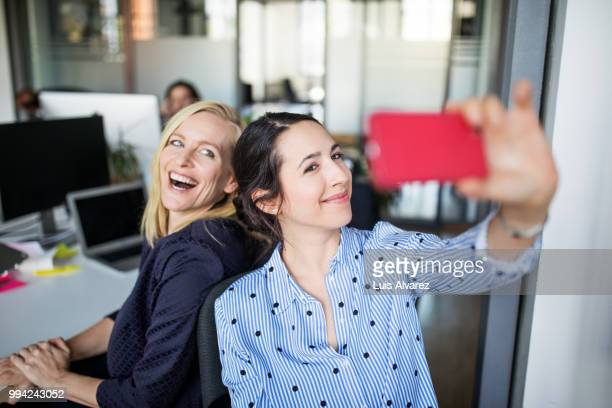 businesswoman taking selfie with female colleague - colega fotografías e imágenes de stock