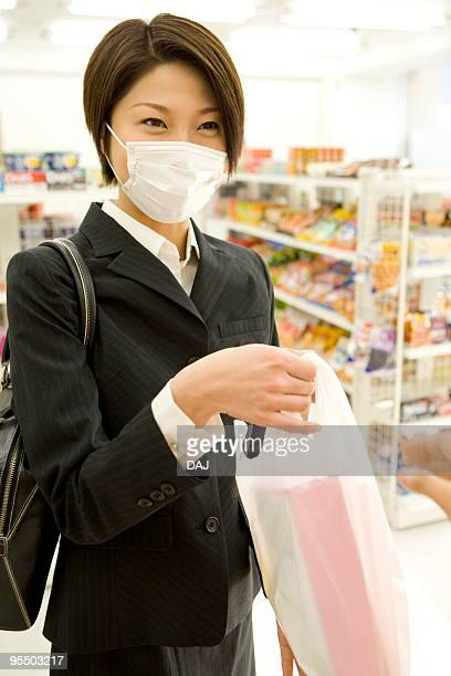 Businesswoman taking stuffed plastic bag from cashier