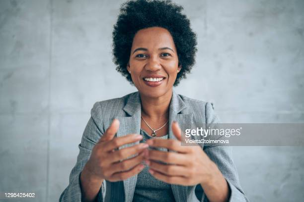 businesswoman talking during video call in the office. - speech stock pictures, royalty-free photos & images