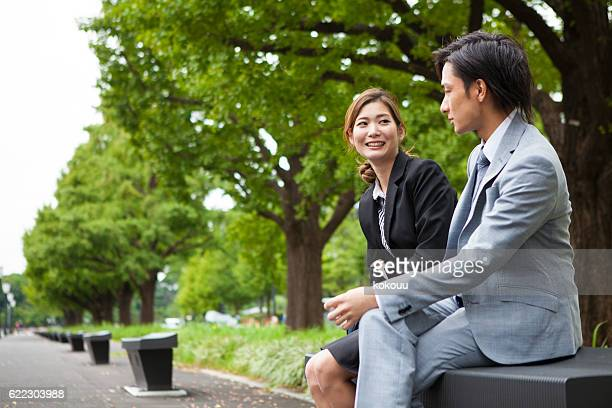 Businesswoman talking happily with a lover in a park