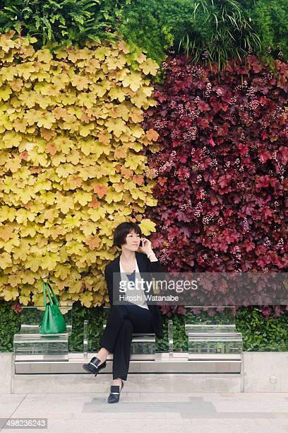 Businesswoman talking in front of green wall