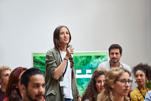 Businesswoman talking into microphone in seminar - gettyimageskorea