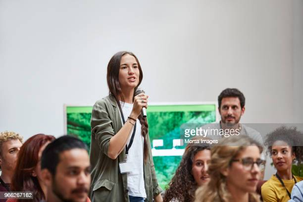 businesswoman talking into microphone in seminar - discurso - fotografias e filmes do acervo