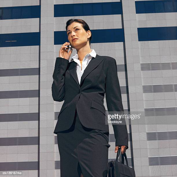 businesswoman talking on a mobile phone standing in front of an office building