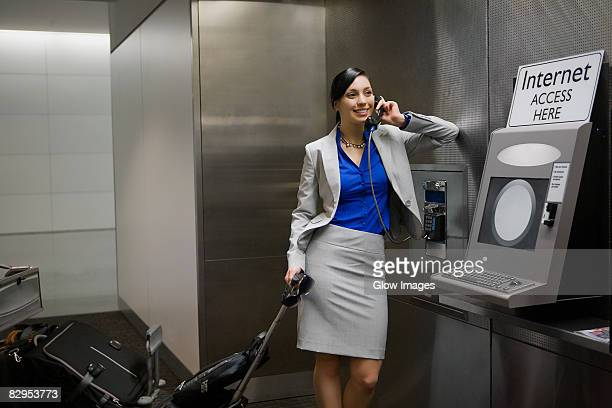 Businesswoman talking on a pay phone at an airport and smiling